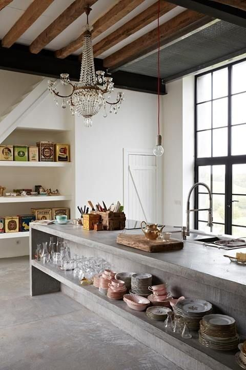 an oversized concrete kitchen islnd with open storage is a bold modern idea