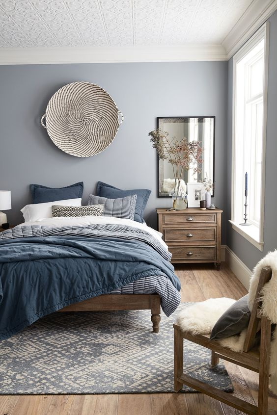 create a soothing space with a grey and blue bedding set with various prints and a navy and neutral rug