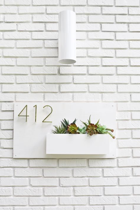a minimalist all white house number design with succulents