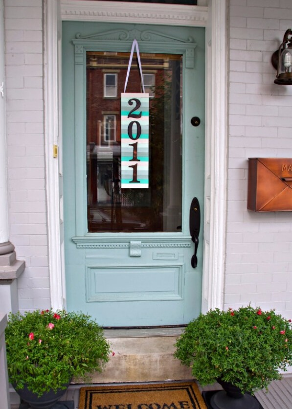 a colorful paint stick sign with house numbers hanging on the front door - a cool idea instead of a wreath on the front door