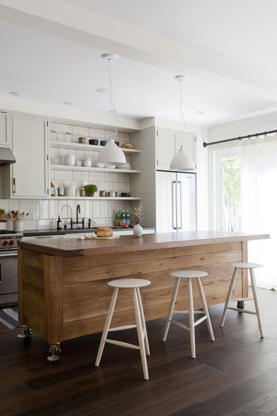 a large kitchen island clad with wood contrasts the neutral kitchen