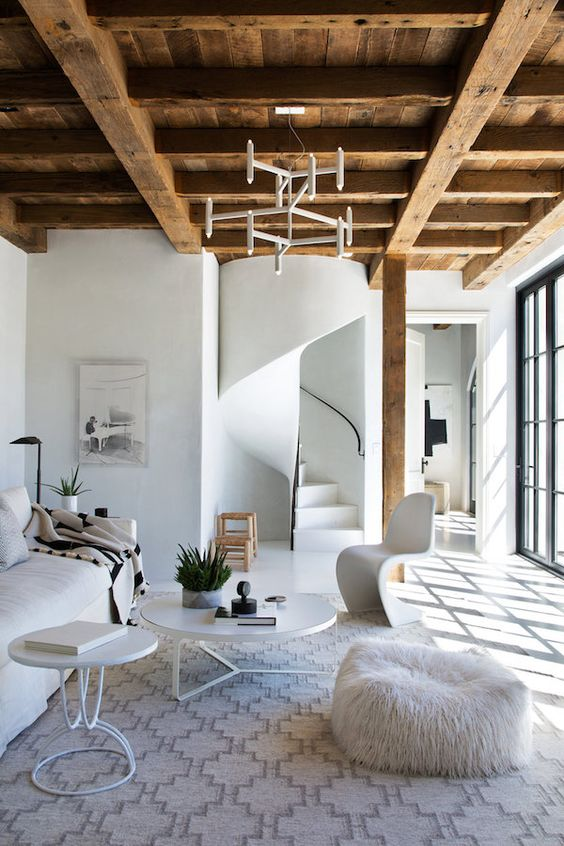 a rustic wooden ceiling with beams is a warm feature that adds coziness to this all-white space