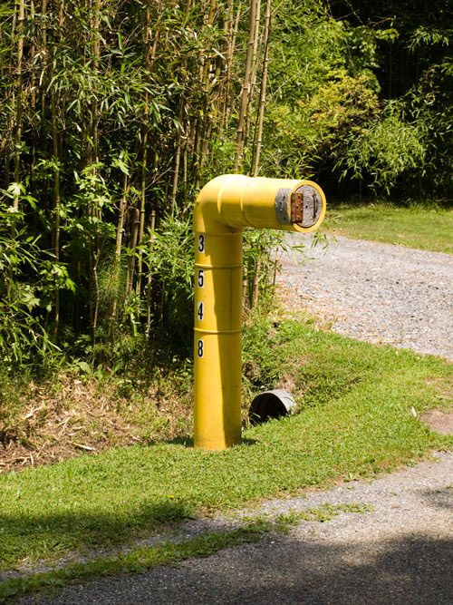 a submarine-inspired mailbox in industrial style, in a bold yellow shade and with house numbers written on it