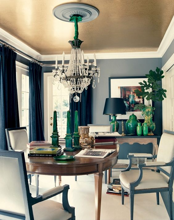 an elegant dining room with refined furniture, a sophisticated chandelier and a gold ceiling
