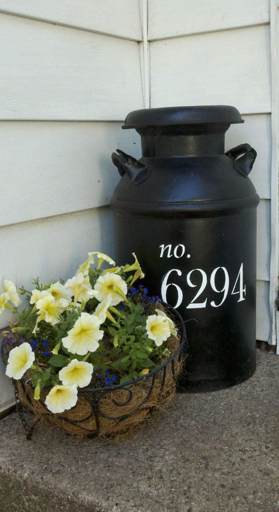 a large black milk churn with white house numbers on your porch is a nice idea to show your address with a rustic feel