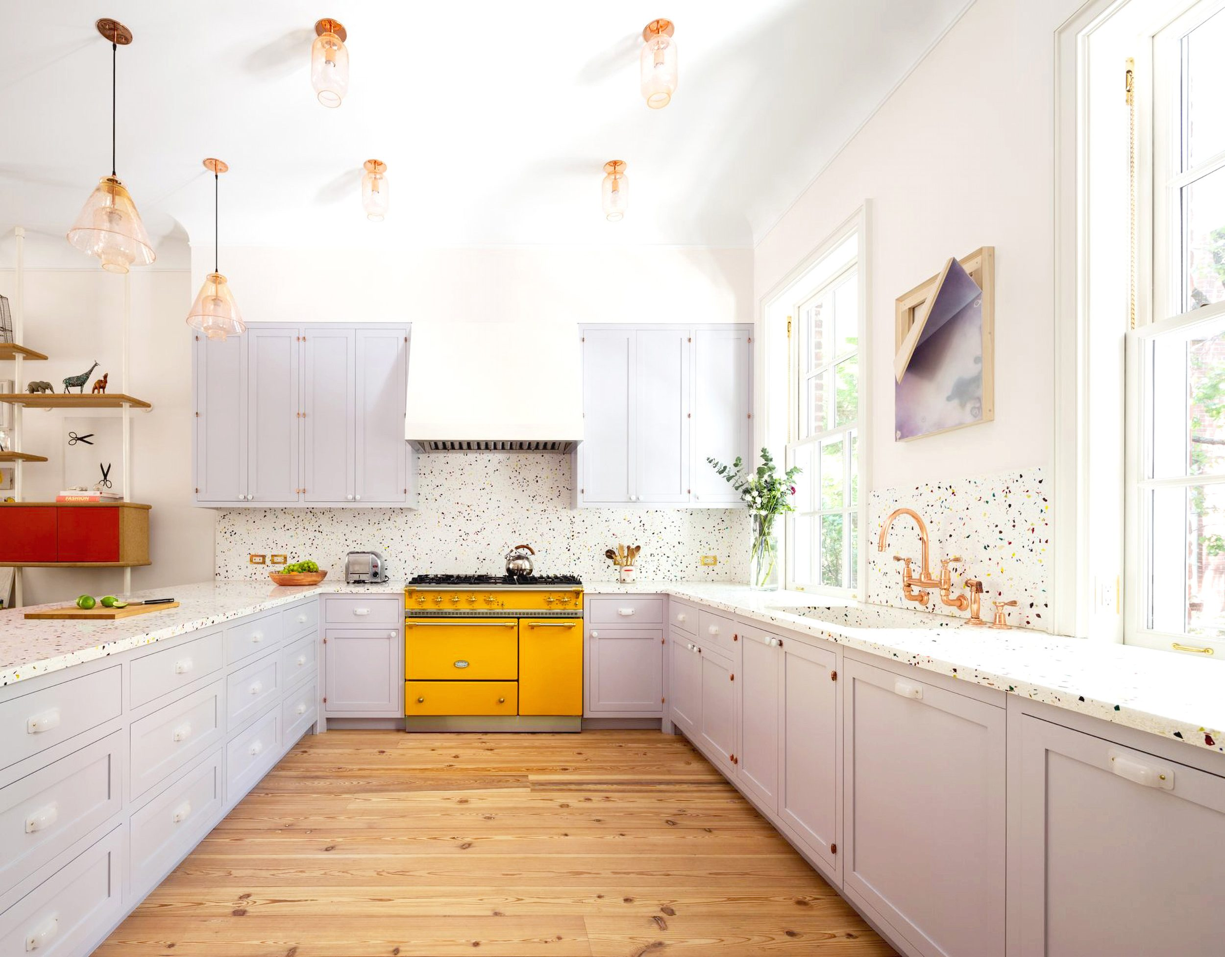 a lilac kitchen accented with a bright yellow cooker and a polka dot backsplash plus brass lamps