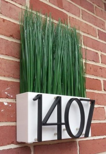 a modern house number idea with a planter with greenery (fake or not) is a cool way to refresh your outdoors