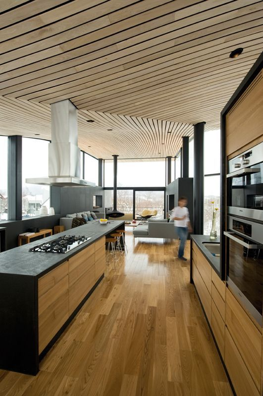 a sculptural plank wooden ceiling brings an edgy feel to the space and contrasts black furniture and pipes