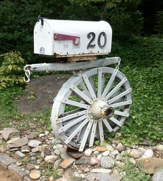 a vintage wheel and a wooden plank to hold a vintage mailbox with house numbers on it   cool for a refined touch