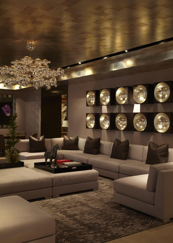 an exquisite and chic living room with a metallic ceiling, a bubble chandelier and wall lamps