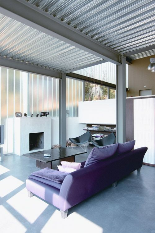 a chic contemporary living room with a corrugated ceiling with metal beams that contrast the furniture