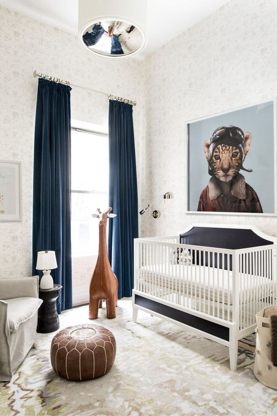 a whimsy modern nursery decorated with a leather ottoman, a large toy giraffe, an artwork and rugs