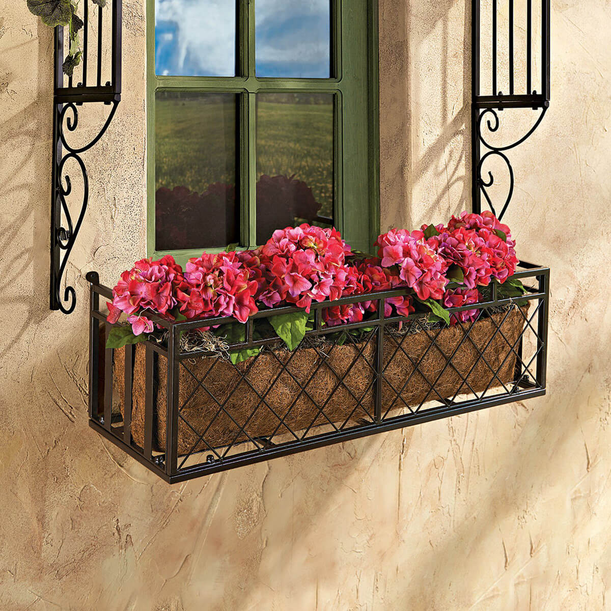 a black metal criss cross window box for potted plants and flowers allows changing the plants whenever you want