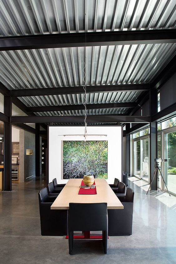 a contemporary dining room with a corrugated steel ceiling that makes the space less formal