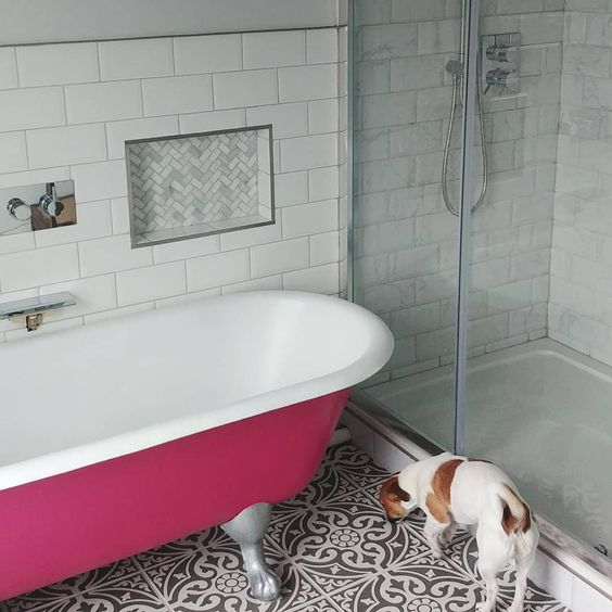 a fuchsia-colored clawfoot free-standing bathtub brings color and a vibrant touch to the space