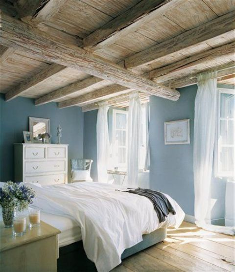 a vintage-inspired bedroom with a rough and rustic wooden ceiling with lots of beams that takes over the space
