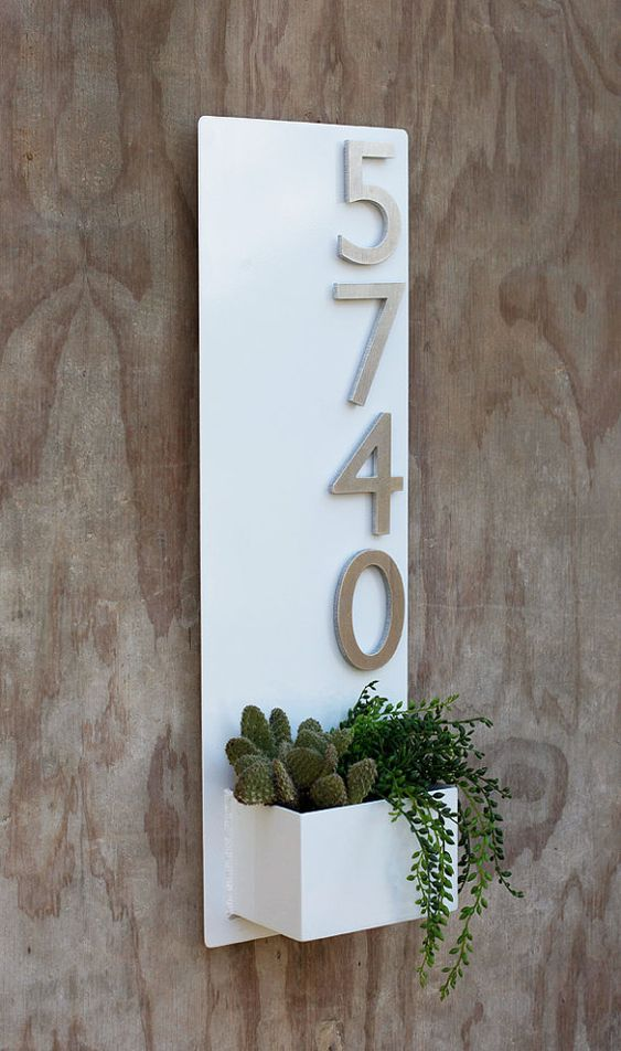 a white wall planter with aluminum numbers and cacti and succulents in the planter for a modern feel