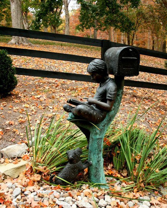 a whole sculpture of a boy and a dog plus s mailbox is a great idea for any outdoor space   it's so dreamy