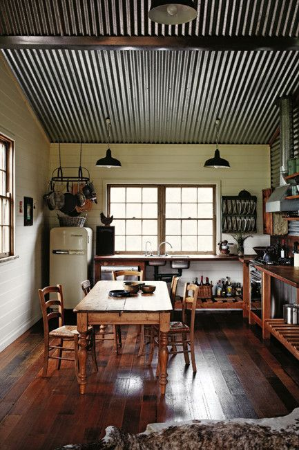 a corrugated steel ceiling with metal beams is a great idea for a sloped roof in your kitchen
