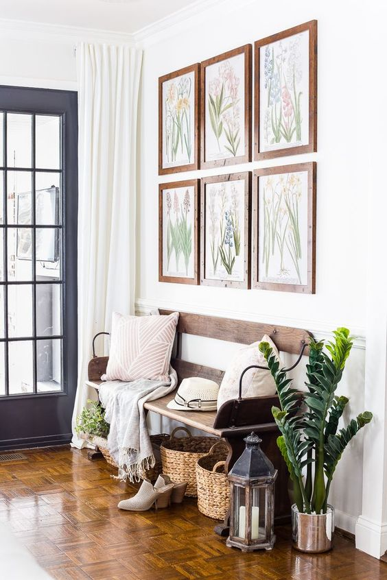 a gallery wall with botanical artworks, potted greenery, lanterns and baskets to accessorize the space