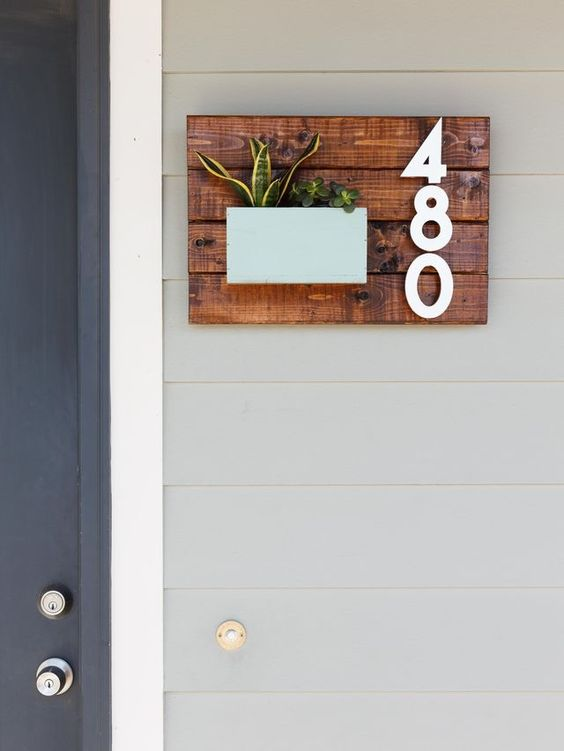 a wooden sign of stained planks, stylish numbers and some succulents in a pastel-colored planter