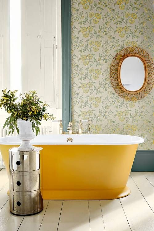 an oval yellow bathtub brigns color to the space, and makes a statement in this bathroom