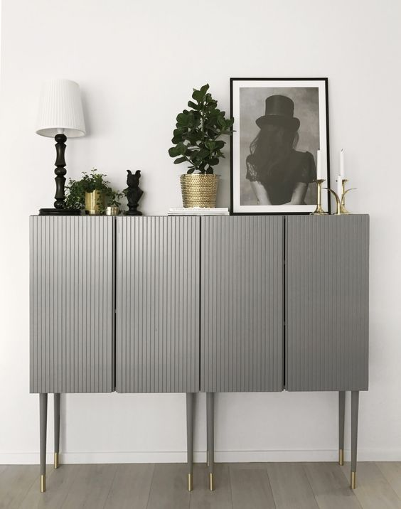 two IKEA Ivar cabinets done in grey with paneling and placed on tall legs look very chic and elegant