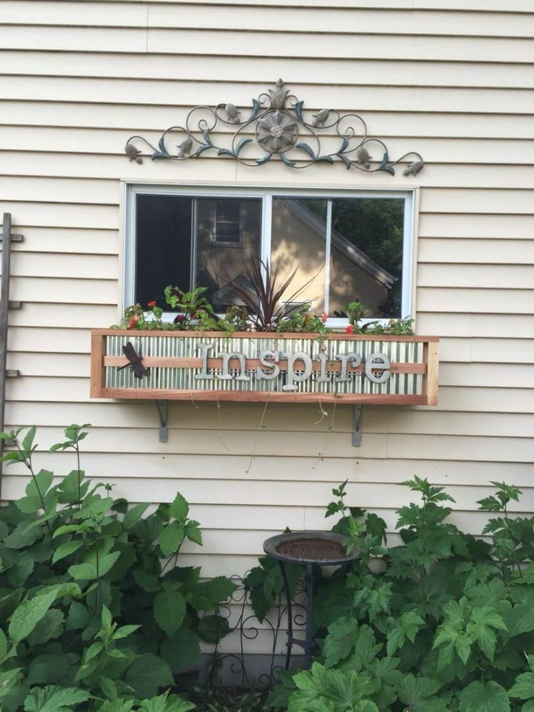 a DIY wood and tin window box planter with greenery and other plants and some letters