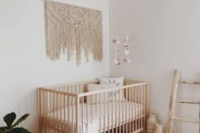 26 a boho baby's room with a wicker lampshade, a macrame hanging, a boho rug and a ladder
