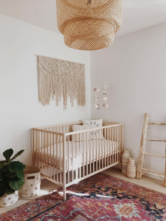 a boho baby's room with a wicker lampshade, a macrame hanging, a boho rug and a ladder