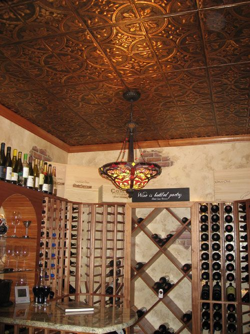 a home wine cellar spruced up with a pressed tin ceiling that gives a chic and vintage feel to the space