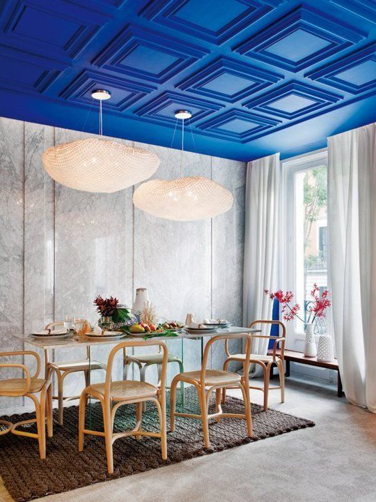 an electric blue paneled ceiling is a major color statement and design feature of the dining room