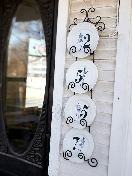 house numbers made up of vintage skeleton stenciled plates displayed on a hangign metal shelf attached to the wall