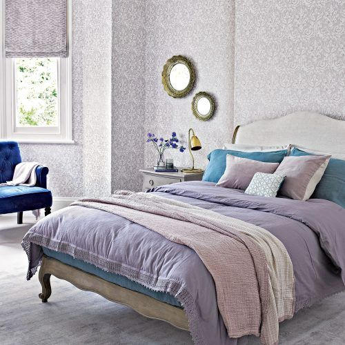 printed lilac wallpaper and Roman shades bring a vintage feel to the space, and lilac bedding helps with that