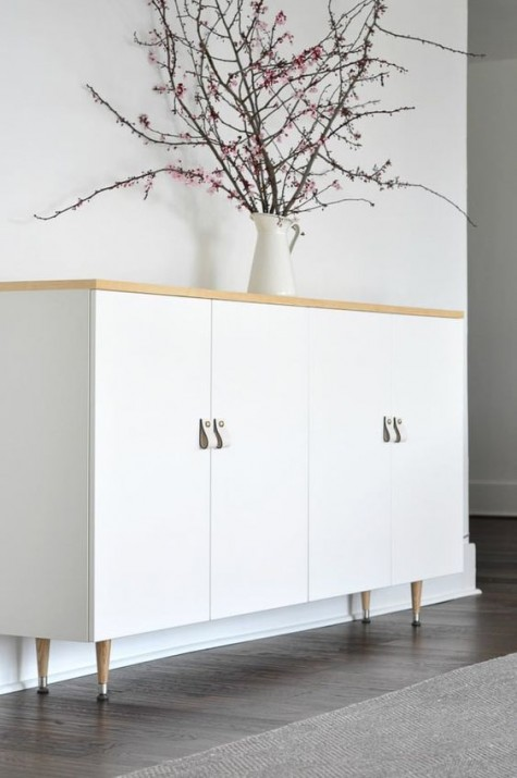 white Ivar cabinets with a wooden top and wooden legs plus white leather pulls look Scandinavian
