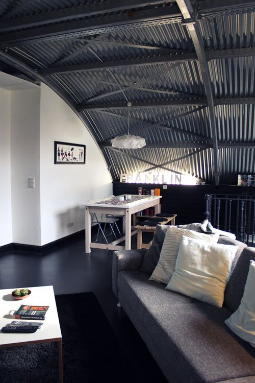 a masculine space with a corrugated steel arched ceiling that adds to the style of the space