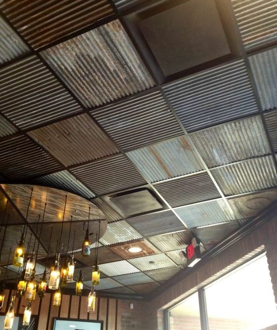 a unique industrial ceiling done with mismatching steel sheets in various colors and an industrial chandelier