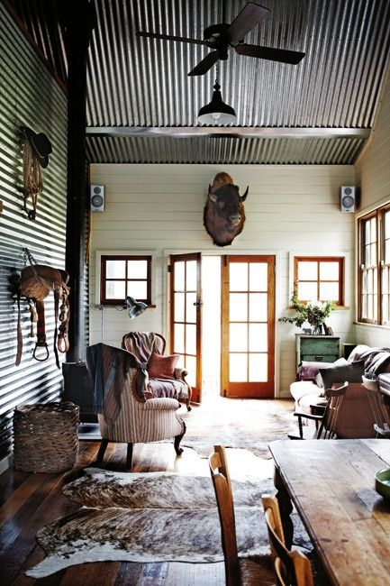 an entryway of a rustic hut with a corrugated steel ceiling and a matching wall for a rustic feel