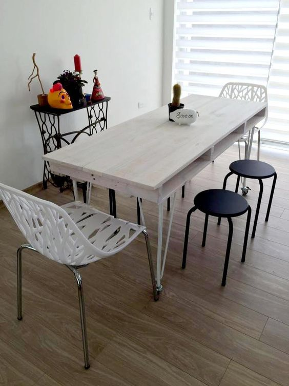 a relaxed whitewashed pallet dining table with a tabletop of a single pallet and thin metal legs on casters