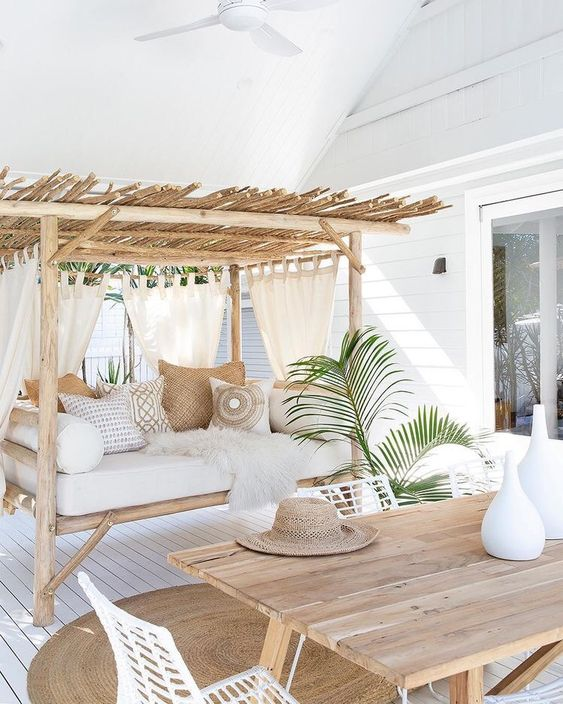 a welcoming tropical terrace with a wooden table, white metal chairs, a bench with a roof and lots of pillows