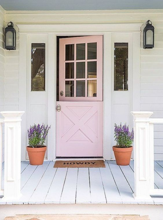 a blush door in farmhouse style, wall lamps and planters with purple blooms for a cozy rustic feel