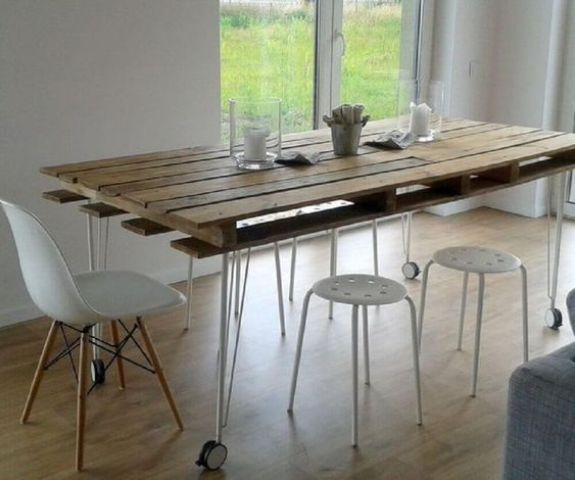 a contemporary dining table with a pallet as a tabletop and hairpin legs on casters plus modern white chairs