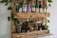 04 a stained wine rack of pallet wood features enough space for bottles and potted greenery on top