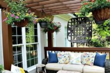 04 a super bright summer deck with ble, yellow and pink highlights, potted blooms hanging down and bright rugs