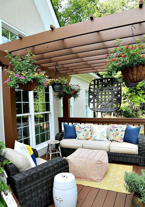 a super bright summer deck with ble, yellow and pink highlights, potted blooms hanging down and bright rugs