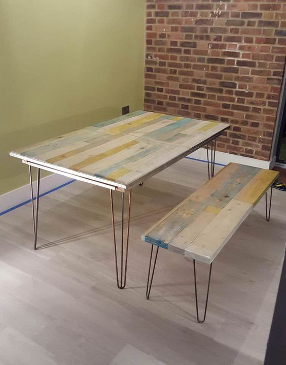an upcycled pallet dining table and matching benches with hairpin legs and touches of whitewashed colors
