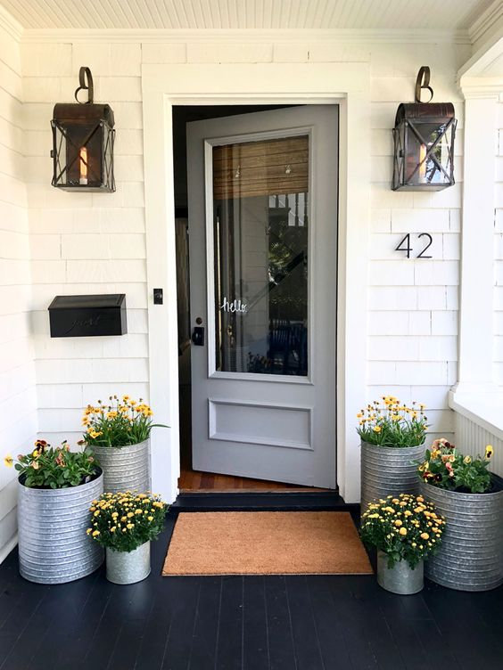 galvanized planters with the same bright blooms give a rustic and cozy feel to the porch