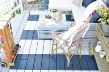06 a nautical summer deck in navy and white, with a striped floor, rattan furniture and pillows