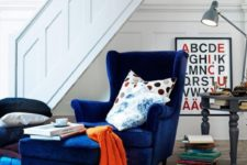 06 a navy velvet wingback chair with a matching ottoman and some colorful pillows for comfortable reading