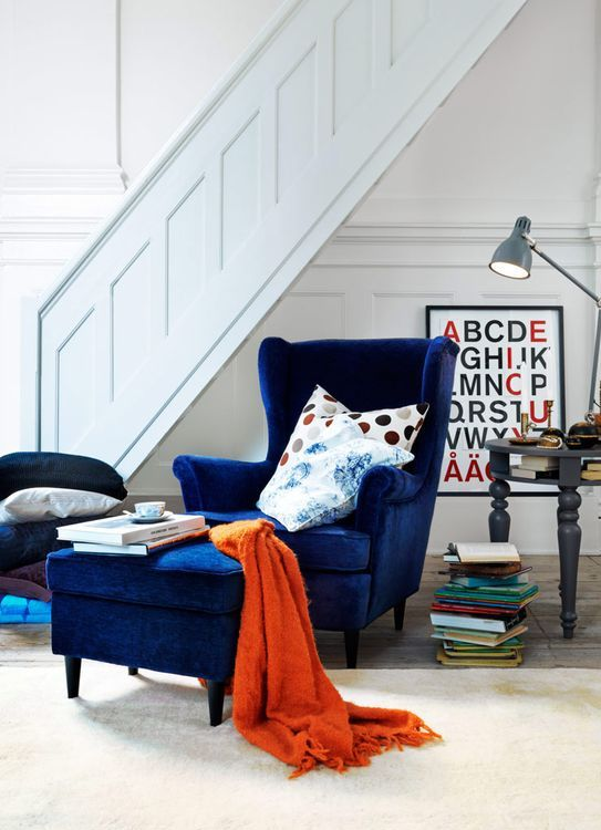 a navy velvet wingback chair with a matching ottoman and some colorful pillows for comfortable reading